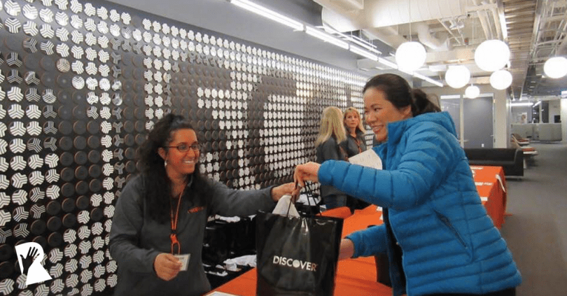 A female employee handing a bag to a woman
