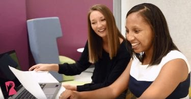 Two female employees working on a laptop in an office