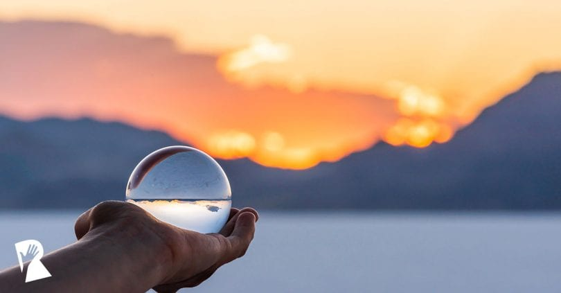 hand holding crystal ball at sunset