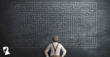 Man trying to solve a labyrinth on a chalkboard