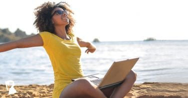 Happy woman sitting on the beach using a laptop