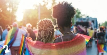 Women hugging Pride parade